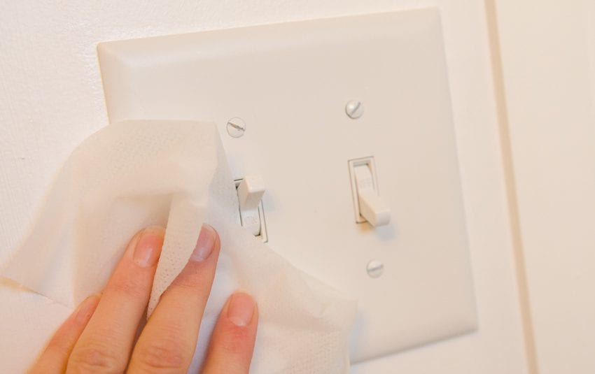 disinfecting and cleaning light switches to help prevent coronavirus covid-19